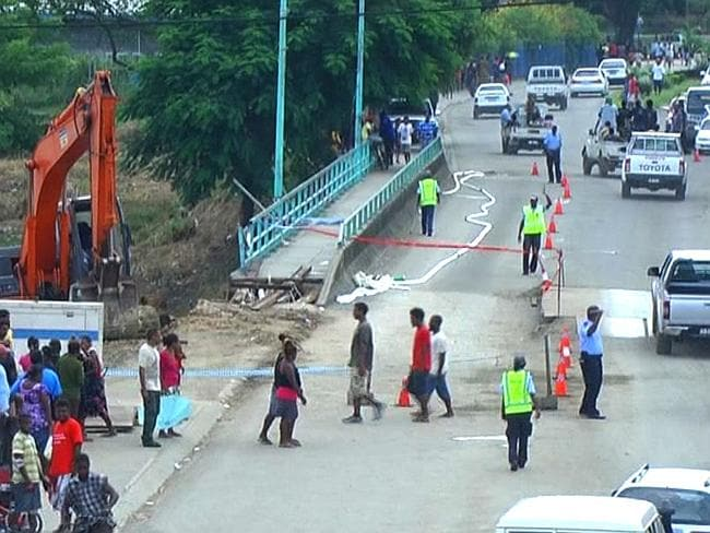Damage ... Police officers control traffic passing over Mataniko Bridge in the Solomon Islands capital of Honiara amid concern it could collapse in the the wake of flooding on April 6. Pic: Dorothy Wickham