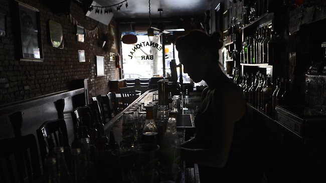 A bartender at the International Bar in the East Village of New York makes drinks in the dark as New Yorkers cope with the aftermath of Hurricane Sandy. Picture: TIMOTHY A. CLARY