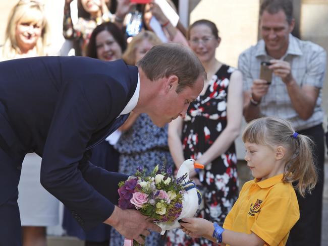 Generous ... a schoolgirl hands Prince William flowers as he arrives at the St. Hugh's College to formally open the Dickson Poon University of Oxford. Picture: AP
