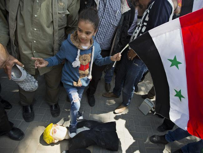 A Palestinian girl holding a Syrian flag tramples on a effigy of Donald Trump during demonstrations following a wave of US, British and French military strikes to punish President Bashar Assad for suspected chemical attack against civilians.
