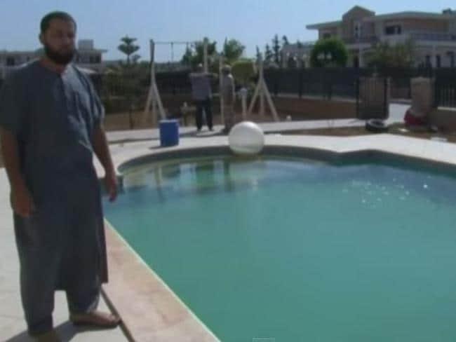 A Dawn of Libya member poses next to the US Embassy pool