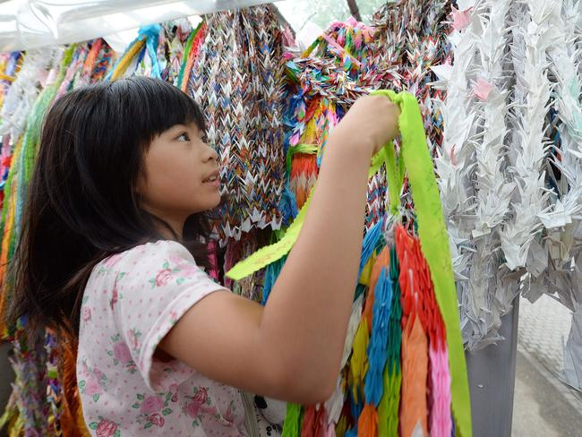 Koharu Morimoto offers colourful paper cranes in honour of the victims of the 1945 atomic bombing. Pic: AFP/ Toru Yamanaka.
