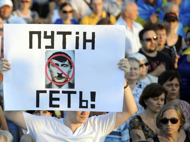 "Anti-Russia ... a man holds a placard reading ""Putin get out!"" during the rally in Mariupol."