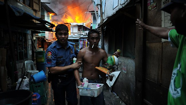 A policeman leads out a resident carrying salvaged belongings from his burning house as a fire engulfs a shanty town in the financial district of Manila.