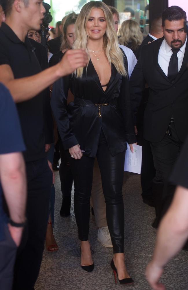 Khloe is walked through the crowd at the event by security.