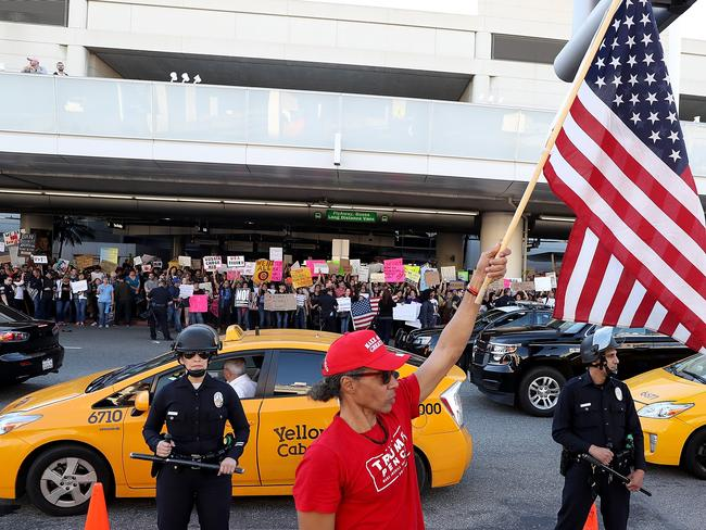 A supporter of US President Donald Trump waves a US flag during a demonstration against the immigration ban that was imposed by President Trump at Los Angeles International Airport on January 29. Picture: Getty