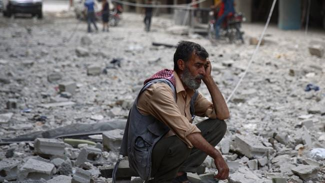 A Syrian man sits amid the rubble of destroyed buildings following reported air strikes by regime forces in the rebel-held area of Douma, east of the capital Damascus. Half of the country's population has been displaced by the war. AFP PHOTO / ABD DOUMANY