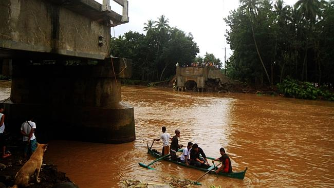 Residents ride a wooden boat as they cross a river after the bridge collapsed overnight due to flooding brought about by heavy rains in Linamon town, Lanao del norte province, in southern island of Mindanao. Picture: AFP