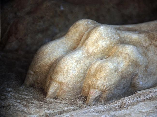 Lion's paw ... A front paw of a large stone sphinx is seen topping the entrance to an ancient tomb under excavation at Amphipolis in northern Greece. Source: AP