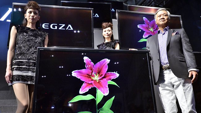 Toshiba executive Masaaki Osumi poses with models next to the company's 55-inch glasses-free 3D TV. Picture: AFP