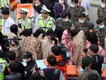 This photo shows rescued passengers, wrapped in blankets, being brought onto land in Jindo after a South Korean ferry carrying 477 passengers and crew capsized on its way to Jeju island from Incheon. Picture: AFP