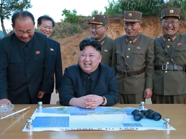 North Korean leader Kim Jong-un (C) reacting during a test launch of a ground-to-ground medium long-range strategic ballistic rocket Hwasong-12 at an undisclosed location. Picture: AFP