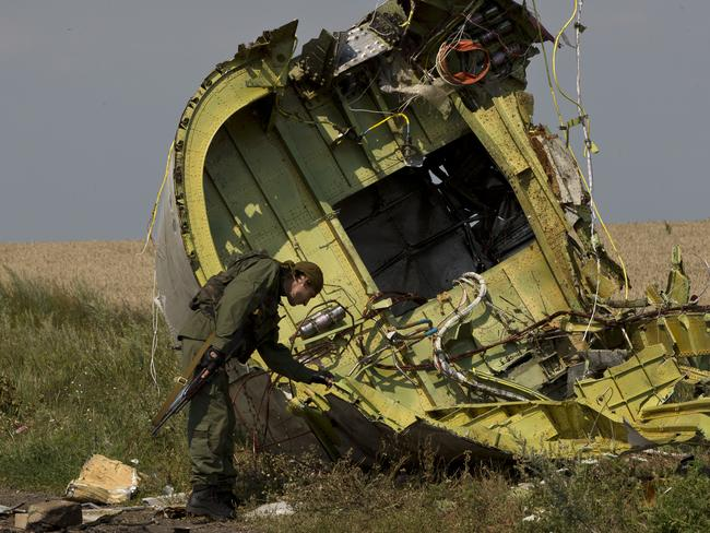 Compromised recovery ... a pro-Russian rebel inspects the MH17 wreckage at the crash site of Malaysia Airlines Flight 17. Picture: Vadim Ghirda