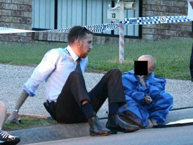 The young boy is comforted outside his home after both his parents were killed. Photo: Glenn Hampson