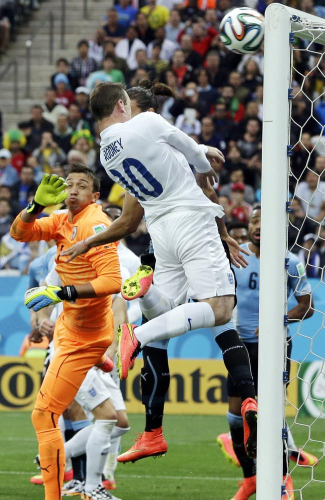 England's Wayne Rooney heads the ball onto the crossbar against Uruguay.