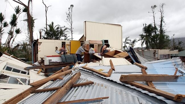 Residents sift through the remains of a house in Tully following Cyclone Yasi. Picture: Jake Nowakowski.