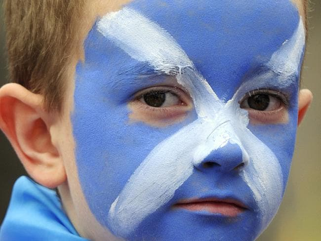 A young boy waits for Team Scotland at the Commonwealth Games parade in Glasgow. Pic: AFP.