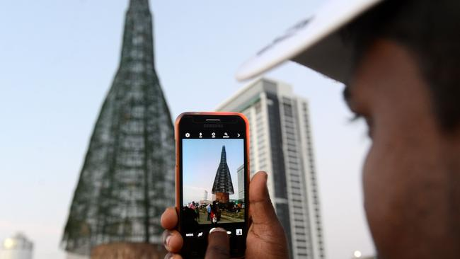 A Sri Lankan man takes a photo of a partially-constructed Christmas tree in Colombo on December 24.