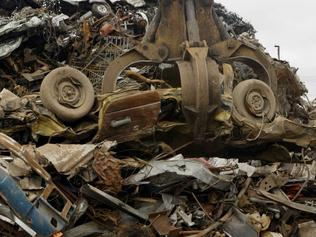 A car that has been crushed gets lifted by a grabber at the Scrap Metal yard in Altona.