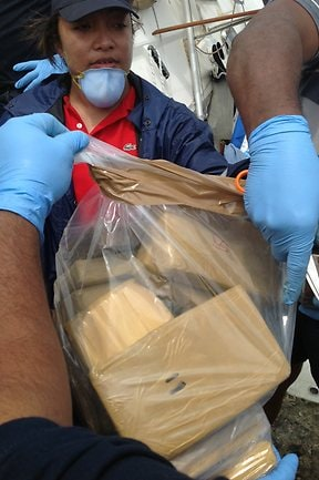 Tongan police officers carry some of the bags of cocaine off the yacht JeReVe that ran aground off the coast near Tonga. Picture: Australian Federal Police