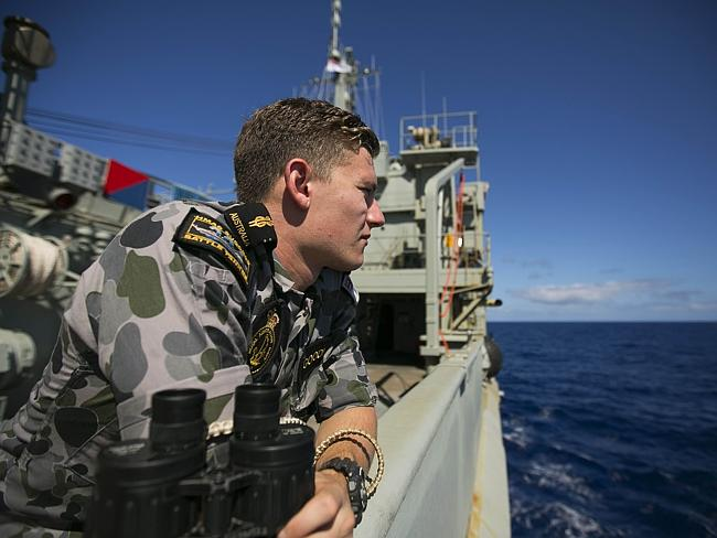 All hands on deck ... Able Seaman Marine Technician Trent Goodman keeps a look out on-board HMAS SUCCESS, scouring the Indian Ocean for the missing plane. Picture: AFP