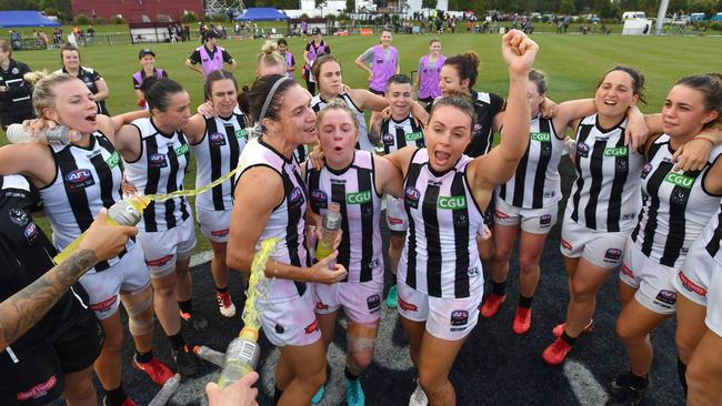 Collingwood players sing the song after their win with debutants Ashl Brazill, Kristy Stratton and Georgie Parker in the middle.