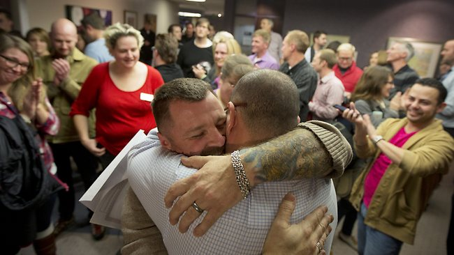 Pure joy...Chris Serrano, left, and Clifton Webb embrace after being married, as people wait in line to get licences outside of the marriage division of the Salt Lake County Clerk's Office in Salt Lake City. Picture: AP