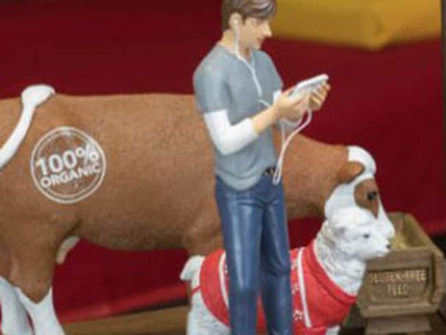 A cow enjoys gluten-free feed while a sheep wears a Christmas jumper. Picture: Modern Nativity