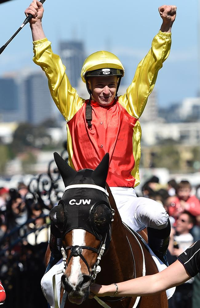 James McDonald raise his arms as the returns to scale aboard the Chris Waller-trained Delectation. Picture: AAP