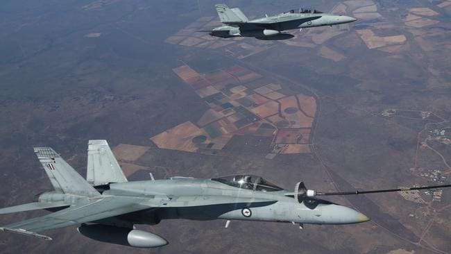 Refuelling in the sky ... RAAF F/A-18 Hornet fighter pilots Flight Lieutenants Chris Chmiel and Bart Langlands fill up from a KC-30A multi role tanker aircraft high above the Northern Territory. Picture: Gary Ramage.