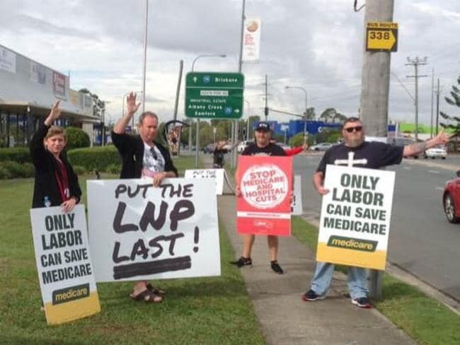 Protesters outside Peter Dutton's office carrying Labor signs as part of a 'co-ordinated protest'.