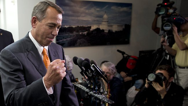 Speaker of the House Rep. John Boehner pumps his fist as he walks past reporters after a meeting with House Republicans as a deal was done to break the US budget impasse. (AP Photo/ Evan Vucci)
