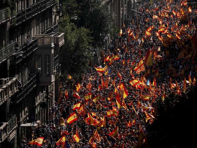 "Protesters hold Spanish flags during a demonstration called by ""Societat Civil Catalana"" (Catalan Civil Society) to support the unity of Spain in Barcelona. Picture: AFP / PAU BARRENA"