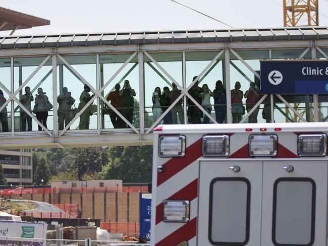 Onlookers ... People watch from a bridge as an ambulance transporting Nancy Writebol arrives at Emory University Hospital in Atlanta. Mrs Writebol will join another U.S. aid worker, Dr. Kent Brantly, in a special isolation unit. Picture: AP