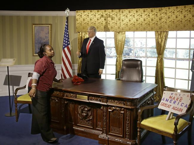 Shameka Nurse, a guest host at the Dreamland Wax Museum, works tending to the Donald Trump wax figure standing in an Oval Office scene at the museum. Picture: AP/Stephan Savoia