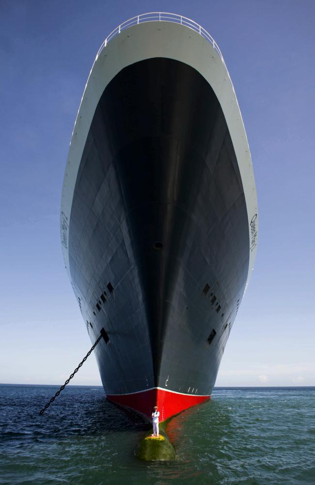 Captain Kevin Oprey stands beneath the soaring hull of the QM2. Picture: James Morgan