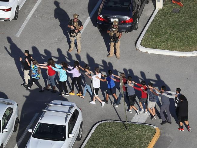 People are brought out of the Marjory Stoneman Douglas High School after a shooting at the school that reportedly killed and injured multiple people. Picture: Getty Images