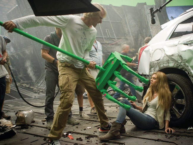 "Director Michael Bay shows Nicola Peltz how the ""hand"" of a Transformer will attempt to grab her."