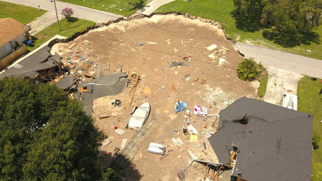 In this aerial photo, debris is strewn about after a sinkhole in Land O' Lakes, Florida. Picture: Luis Santana/Tampa Bay Times via AP