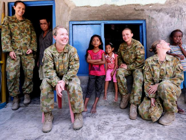 All smiles ... Australian soldiers SIG Kylie Grimes, CPL Kylie Collingwood, LCPL Peta Reeves and SIG Krystelle Watts in a local community in Dili, East Timor in 2013.