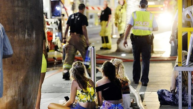 Schoolies sit on the footpath following the emergency evacuation. Picture: