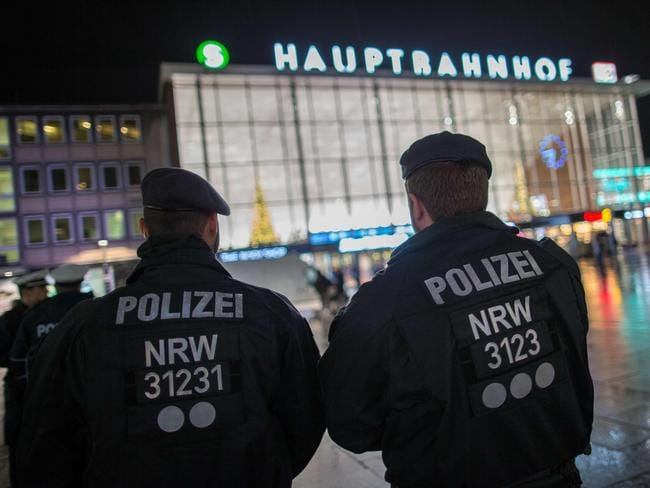 Police officers survey the area in front of the main train station and the Cathedral in Cologne. Picture: AFP / DPA / Maja Hitij