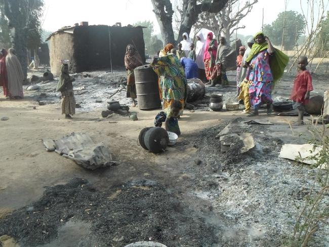 Women and children look at burnt out houses following an attack by Boko Haram in Dalori village. (AP Photo/Jossy Ola)