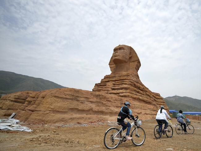 Copycats ... people cycle past a full-size replica of the Great Sphinx of Giza in a village near Shijiazhuang, in northern China's Hebei province.