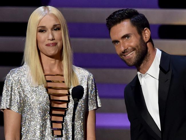 Gwen Stefani and Adam Levine on stage presenting an award to Steven Colbert.