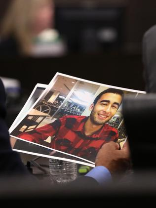 Pedro Bravo's defence attorneys look at a photo of slain student Christian Aguilar. Picture: Doug Finger