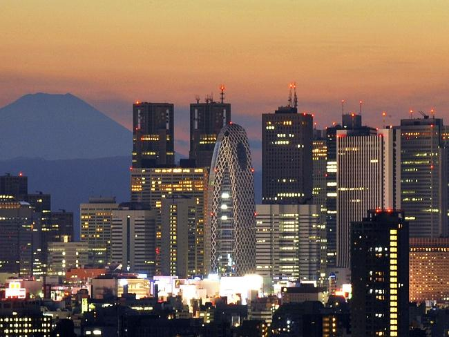 Japan's highest mountain Mount Fuji rises up behind the skyscraper skyline of Tokyo.