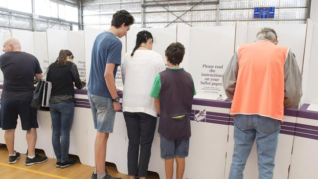 Greens Candidate for Batman Alex Bhathal (white shirt) votes, while her sons Ravi and Patrick look on at the Preston West Primary School polling booth, Melbourne (AAP Image/Ellen Smith) NO ARCHIVING