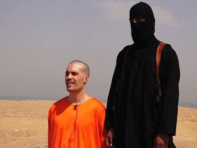Guilty of being in the wrong place at the wrong time ... US journalist James Foley with a black-hooded member of Islamic State, dubbed Jihadi John, before his death. Picture: Twitter