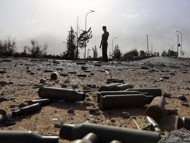 Battlefield ... Spent bullet shells litter the ground as a member of the Islamist-linked militia of Misrata walks past after three days of battles in the area of Tripoli's International airport. Picture: AFP PHOTO/MAHMUD TURKIA